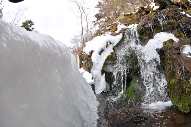 Buz tutmuş kaynak suyu yol boyunca dere olmuş akıyor.