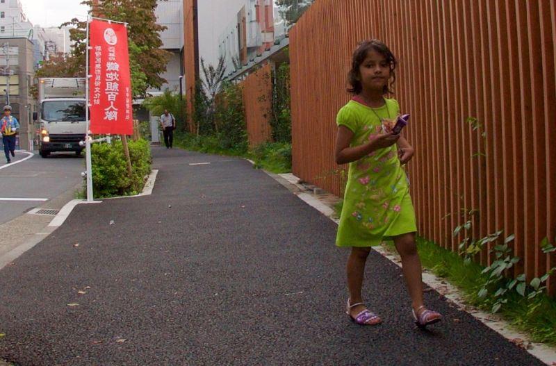 Küçük bir kız dondurmasını yiyerek evine dönüyor
