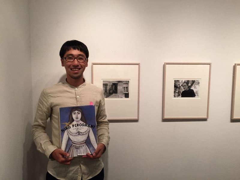 Masashi Gürcü ressamın kitabı ile poz veriyor.