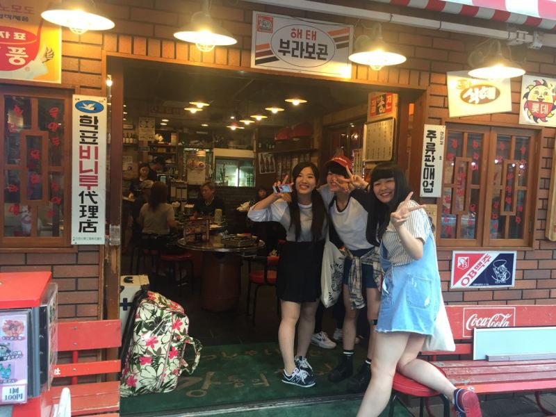 Bir Kore lokantasının önünde poz veren kızlar