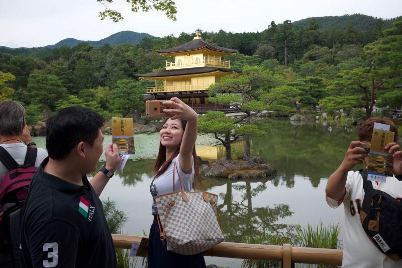 """Kyoto'nun meşhur """"Kinkakuji"""" tapınağı önünde selfie çektiren Çinliler."""